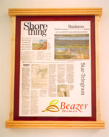 A print of a newspaper article mounted in a custom wood frame