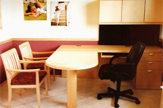 A typical Novikoff Furniture Metaplan desk in a light wood color with two guest chairs an one executive chair