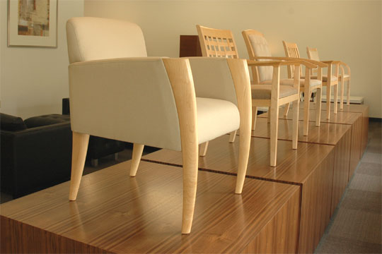A row of upholstered wood chairs on pedestals at the entrance of the Novikoff Furniture showroom