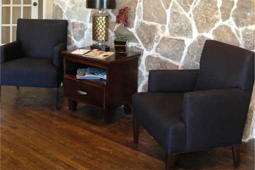 Two Novikoff Furniture lounge chairs with square arms and backs and wood legs