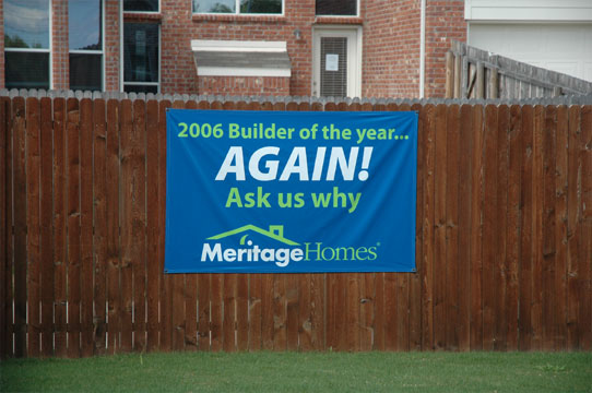 A blue banner mounted on a wood fence