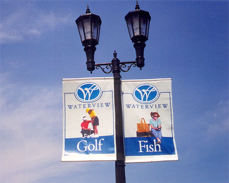 Two banners mounted side-by-side on a light post