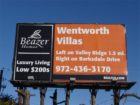 A red and black Beazer Homes billboard mounted on telephone posts