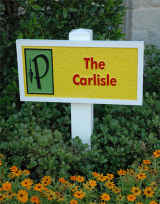 A small sandblasted and painted sign placedin a flower bed