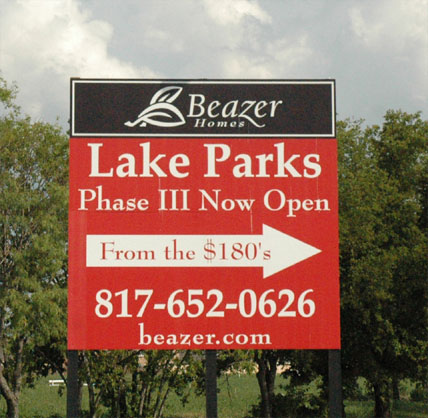 Large red and black directional sign for Beazer Homes with an arrow pointing to the right