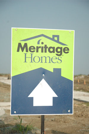 A blue and green Meritage Homes directional sign pointing straight ahead