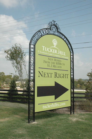 A large black and green directional sign with a large arrow pointing to the right in an elegant frame with scrollwork