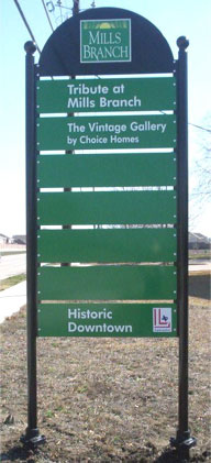 One of the Mills Branch kiosk-style directional signs with green blades mounted on two black posts