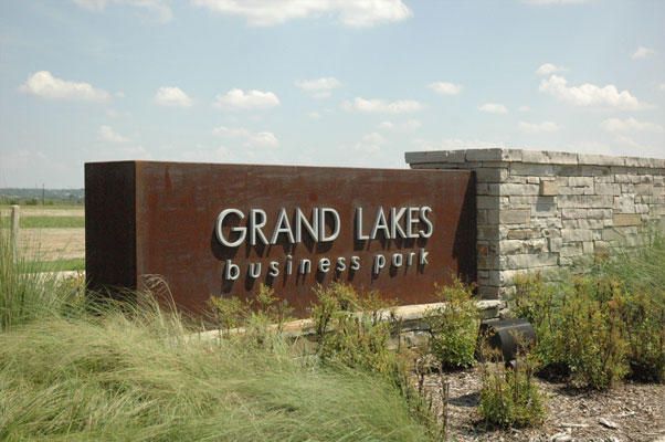 Grand Lakes Business Park monument with aluminum letters mounted to a rust-colored metal box
