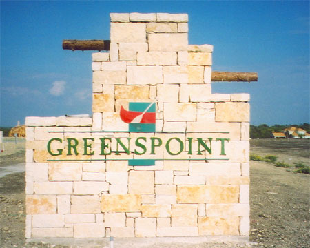 Staircase-shaped stone monument with the Greenspoint logo mounted on the front